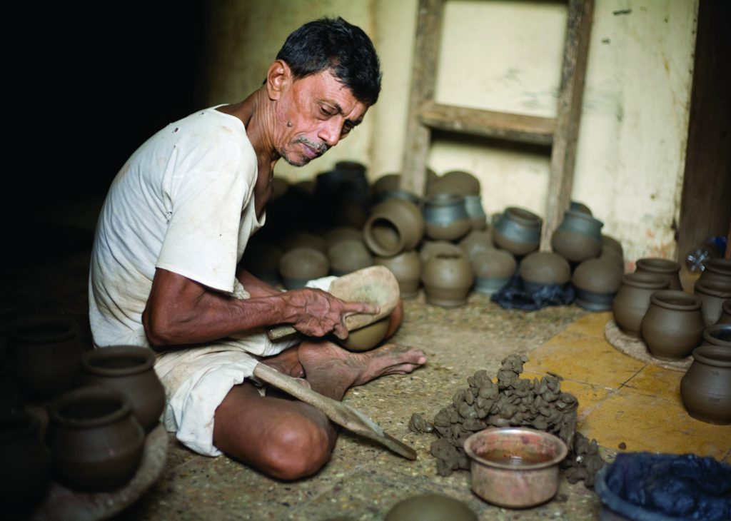 Dalit making clay pot